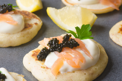 blini with caviar and smoked salmon on table