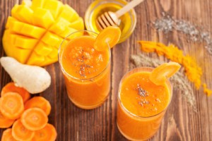 Smoothie with carrot, turmeric, mango, ginger, honey, chia seedss and spices on rustic wooden table